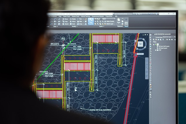 Engineer with Schematic Displayed on Computer