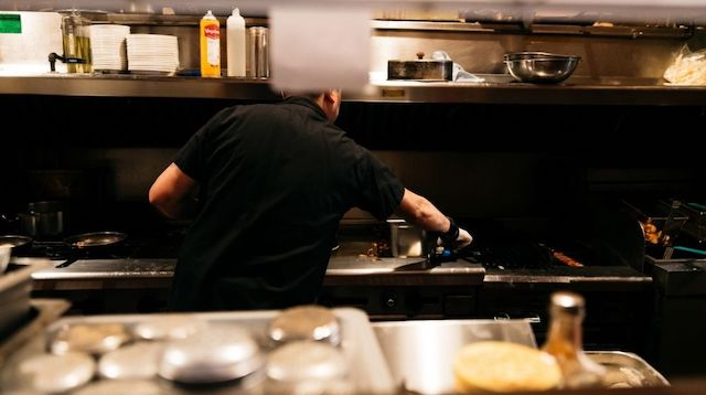 Man Working at a Grill with His Back to the Camera