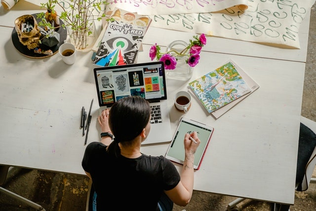 Overhead view of a graphic designer working at a table