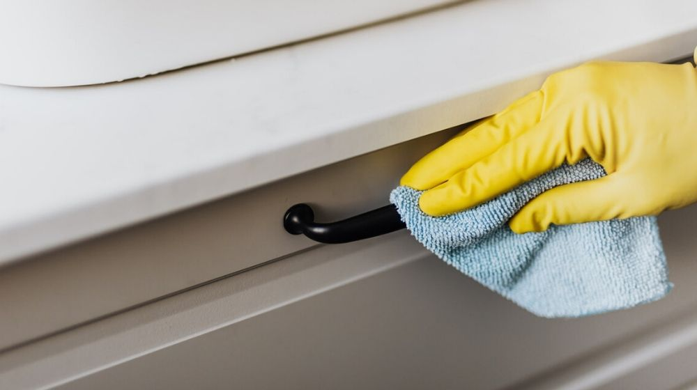 Person Wearing Glove Cleaning a Drawer Handle