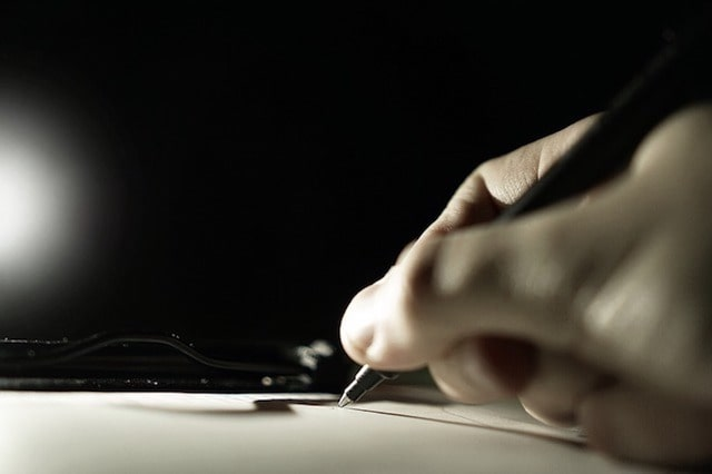 Photo of Person Signing a Clipboard