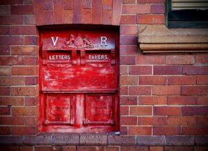 Red post box set into brick wall