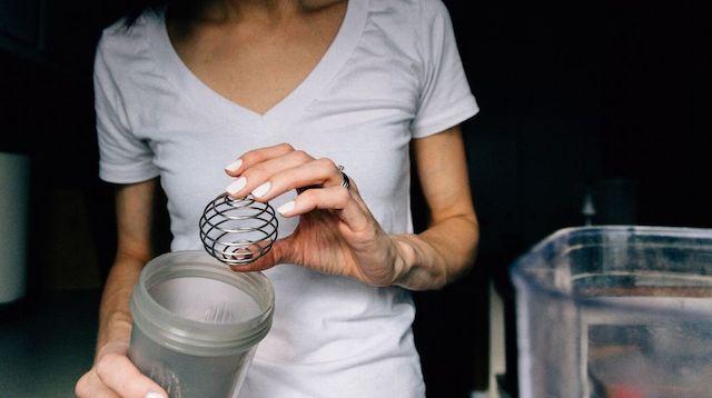Trade Secrets Woman Holding Protein Shake Mixer