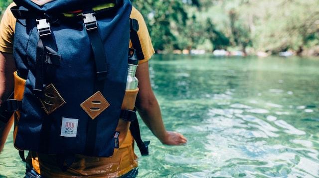 Travel Blog Backpacker Wading in Stream