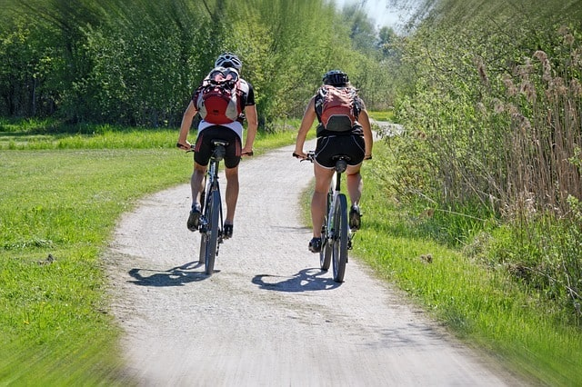 Two People Riding Bikes On A Path