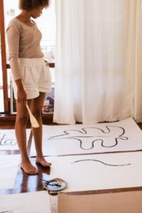 Woman Creating Art on Large White Sheets of Paper