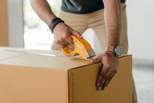 Close-up of a man taping up a shipping box