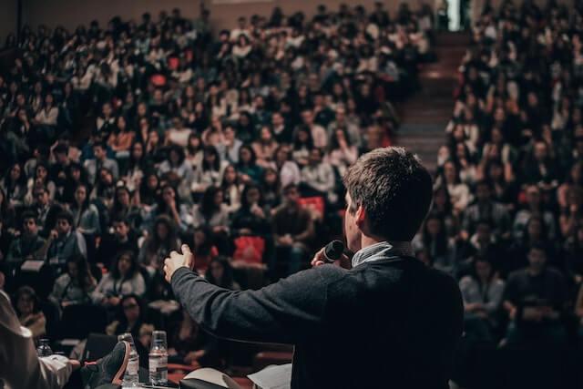 Man giving speech to auditorium full of people