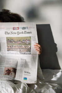 Person reading newspaper while sitting in bed