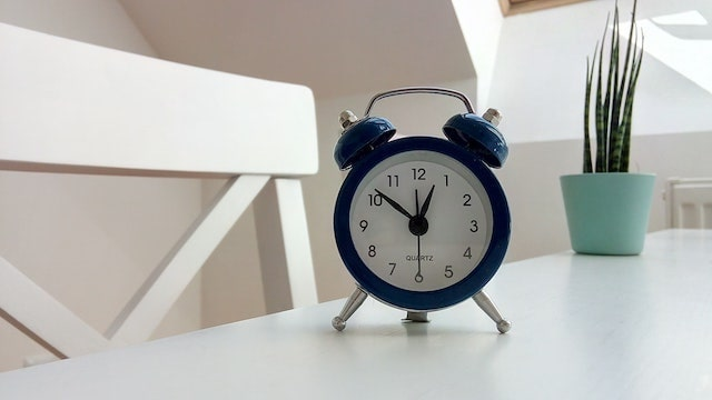 Blue alarm clock sitting on white desk