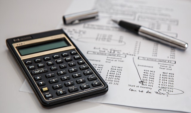 Calculator and budget sheet with pen in the background