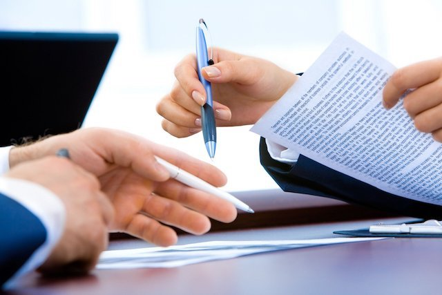 Close-up of two people holding pens and reviewing paperwork