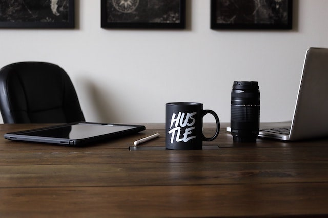 """Desk with coffee mug that reads""""hustle"""" on it"""