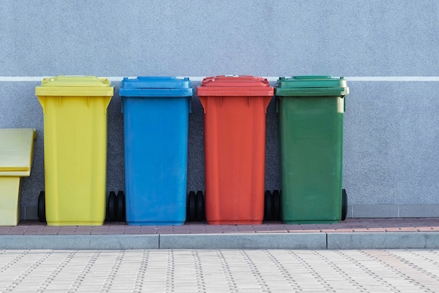 Different colored waste management bins