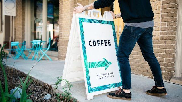 Man setting up coffee shop sign on sidewalk