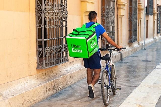 Man with an Uber Eats backpack walking a bike