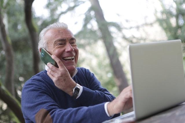 Older man using laptop while talking on smartphone.