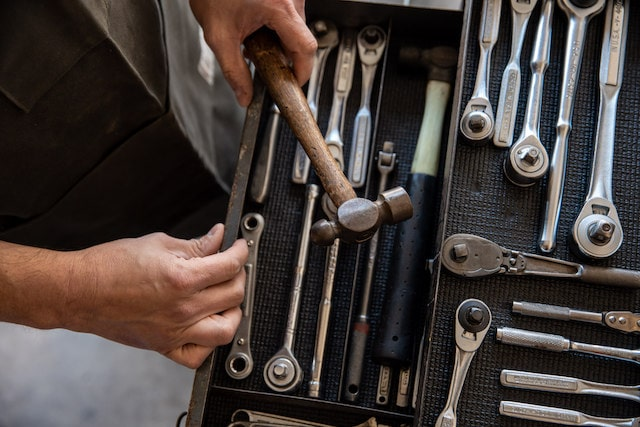 Person holding a hammer over an open toolbox