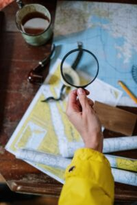 Person holding a magnifying glass to a world map.