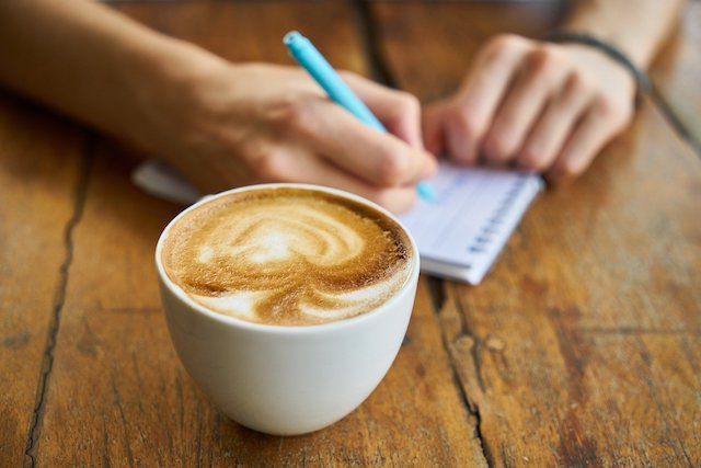 Person with a cup of coffee and a notepad