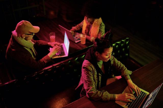 Three people typing on laptops in close proximity to one another